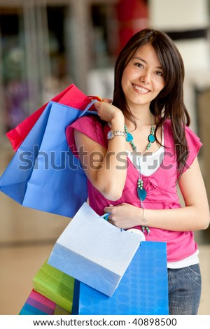 Shopping woman with bags smiling at the mall
