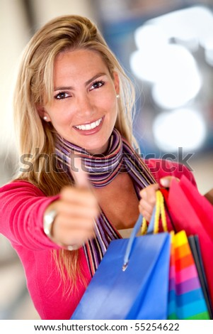Shopping woman with thumbs up at a mall smiling