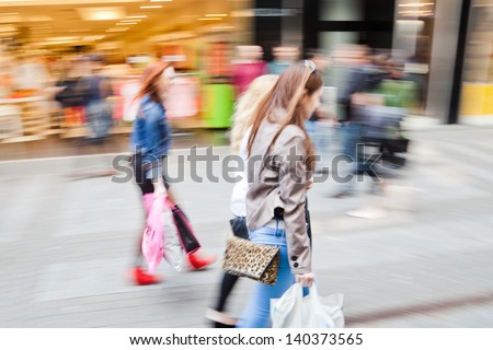 shopping women in motion blur in a shopping street of the city