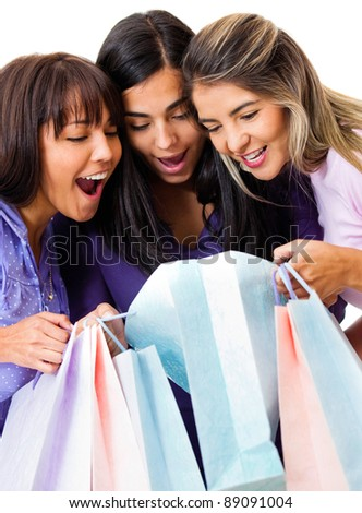 Shopping women looking at purchases inside the bags - isolated over a white background