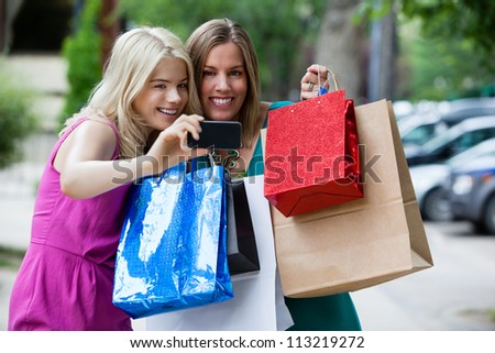 Shopping Women taking self portrait with cell phone.