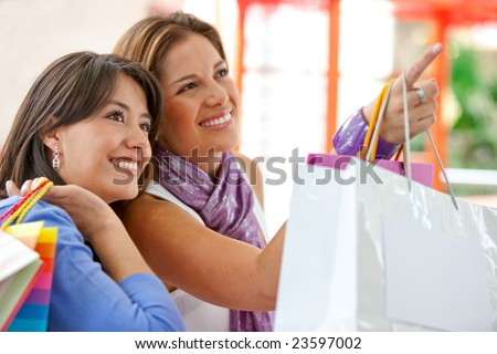 Shopping women with bags pointing out something on a shop window