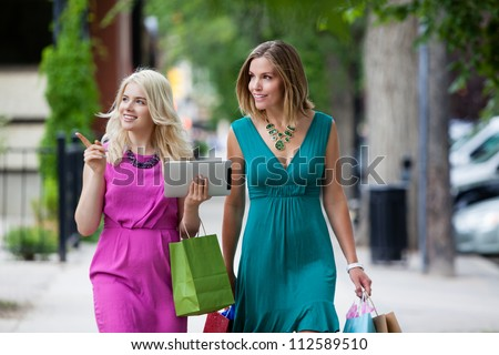 Shopping Women with Digital Tablet on street.