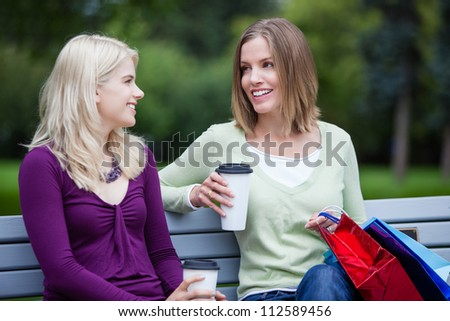 Shopping Women with Takeaway Coffee on bench.