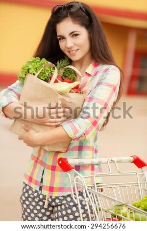 Shopping young woman in store with bags of vegetables, happy girl in supermarket, female customer at market buying vegetables, woman holding shopping basket in supermarket, instagram style filters