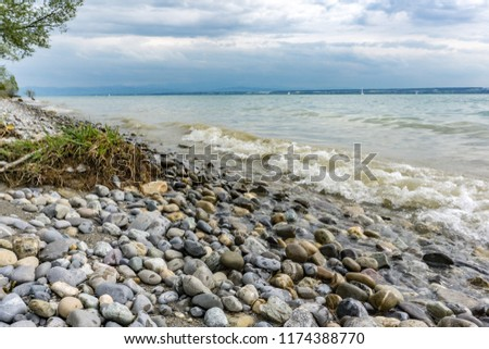 Shore Line with colorful stones. Nice stone Beach at lake constance. Mini waves. #1174388770