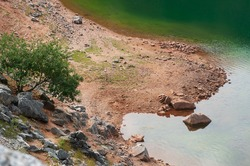 Shore of a small glacial lake with greenish waters between mountains.