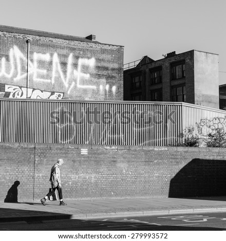 Shoreditch, London, UK - April 18 2015: Young punk rock guy walking in Shoreditch. Shoreditch is one of London\'s most distinctive areas, home of a big hipster community. Black and white.