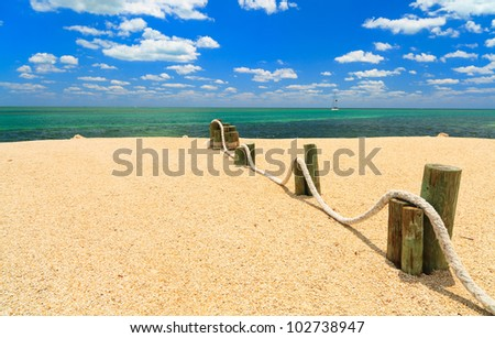 Shoreline of the Florida Keys with sailboat in the background against a blue sky.