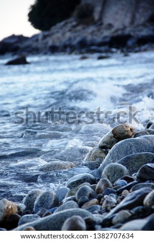 Shores of the Aegean sea. Stone beach. The wave rolls on the shore. Travel and tourism business. #1382707634