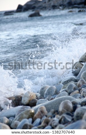 Shores of the Aegean sea. Stone beach. The wave rolls on the shore. Travel and tourism business. #1382707640