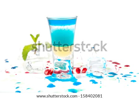 short blue coctail with ice and color drops on white