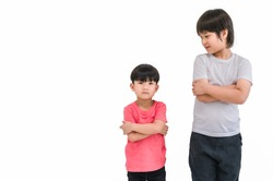 Short child boy in red t shirt and tall child boy in white t shirt standing arms crossed and looking face isolated on white background. Big and small kid concept at be friends. Different boy at tall.