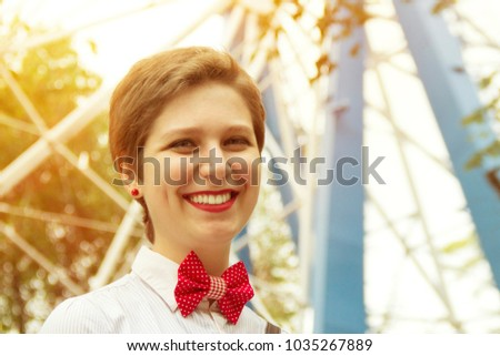 Short-cut young girl in an amusement park. The work of the animator. Concert make-up, a charming smile and a red butterfly. Actress smiling at the amusement park administrator.