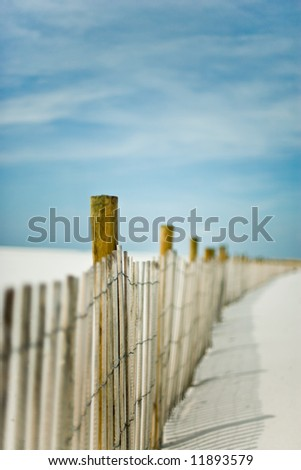 "Short depth-of-field shot of a sand dunes ""fence"" at the beach. Simple, abstract view, mood shot, lots of sky and sunlight and space."