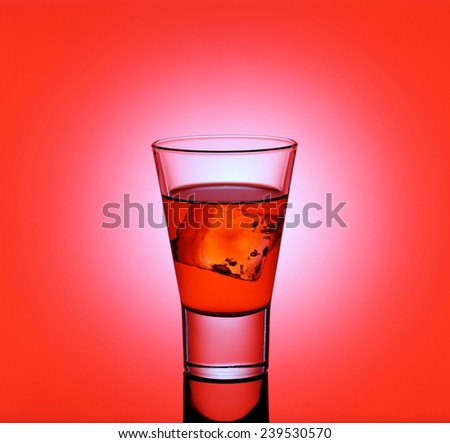 Short drink glass with red liquid and ice cubes, red background