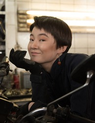 short-haired Asian working girl in a car service, blue working overalls, near a motorcycle
