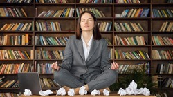 Short haired businesswoman meditates sitting in yoga pose on wooden table among rumpled paper sheets and laptop against bookshelves close-up