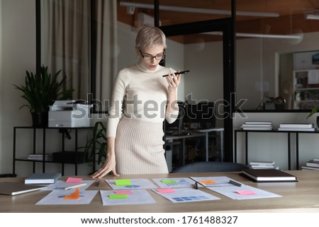 Short-haired confident businesswoman hold smartphone activate virtual digital assistant search helpful info in internet do project presentation preparation, has business distant talk using loudspeaker Foto stock ©
