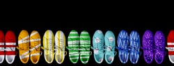 Short low brigt multicolored sneakers on a black background. Seamles. Rainbow
