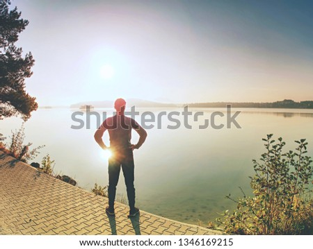 Short pause. Male long distance runner in endurance training at mountain lake in summer nature.  #1346169215