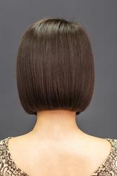 Short symmetric brunette bob hair of young wonam back view on gray background.