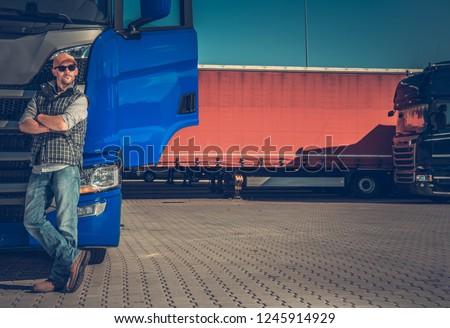 Short Truck Stop Break. Caucasian Semi Trucker in Front of His Modern Truck Tractor.
