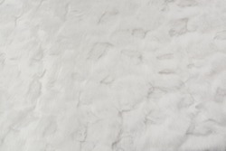 Short white wool, can be used for sewing toys. Faux fur fabric. Artificial fur fabric texture with gradient in natural colors, useful as a background.