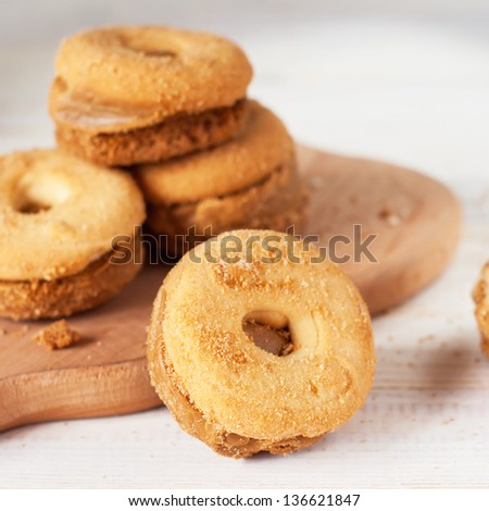 Shortcake in the circle form on the white wooden table, square image