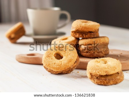 Shortcake in the circle form on the wooden table with cup of tea