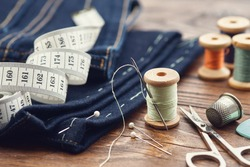 Shortening jeans. Measuring tape, scissors, spools of thread, thimble, including pins and chalk on table. Jeans cutting.