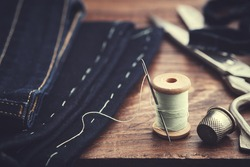 Shortening jeans. Wooden spool of  thread, thimble and scissors on table . Jeans cutting.