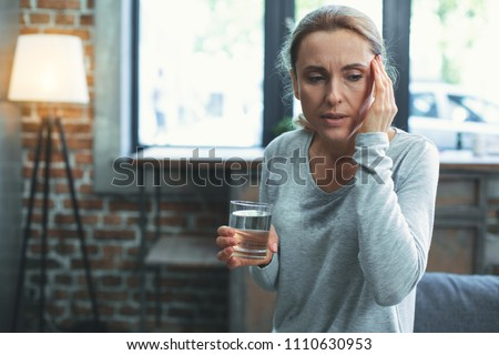 Shortness of breath. Unhappy mature woman sweating and touching head #1110630953