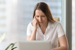Shortsighted businesswoman squinting eyes looking at pc laptop screen while sitting at home office, tired of computer thoughtful woman having poor weak eyesight, bad sight, blurry vision, need glasses