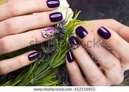 Shot beautiful manicure with flowers on female fingers. Nails design. Close-up. Picture taken in the studio on a white background. #612116855