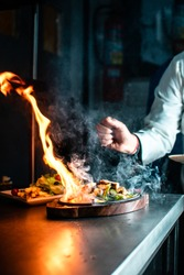 Shot from an Indian restaurant where chef is making smoky sizzler, as fire catches when he puts hot butter over grilled chicken.