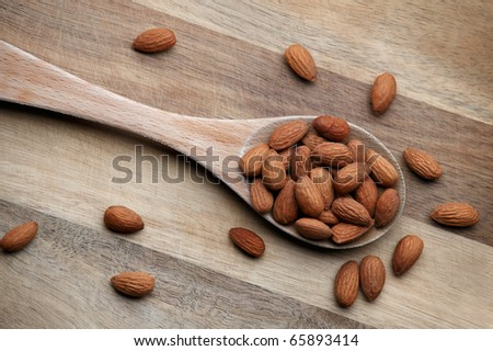 Shot from directly above. Almonds are packed into a wooden spoon, which is photographed diagonally through the image. Scattered almonds for effect and fill.