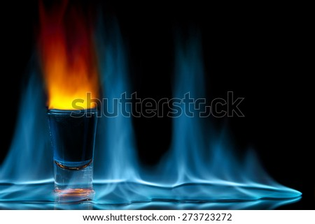 shot glass on fire against black background