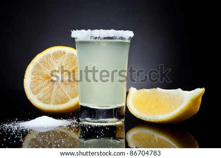 Shot glass with a lemon on black background