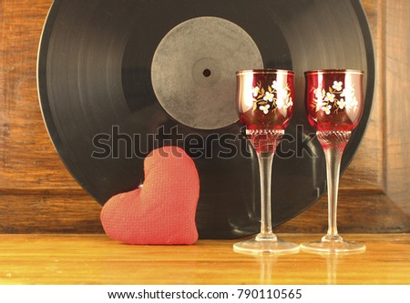 Shot-glasses stand onthe old table. Background old vinyl record. #790110565