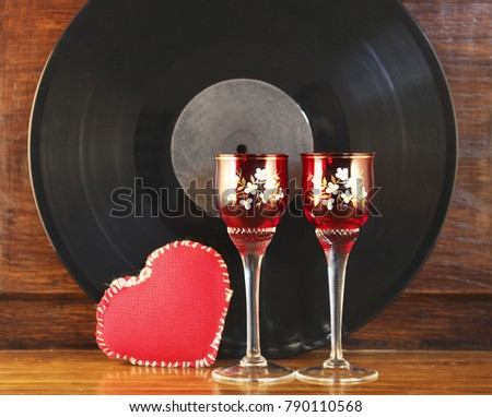 Shot-glasses stand onthe old table. Background old vinyl record. #790110568