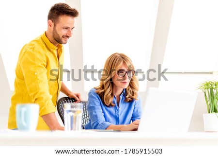 Shot middle aged busineswoman working on laptop while her colleague standing next to her and consulting about business plan. Teamwork in the office.