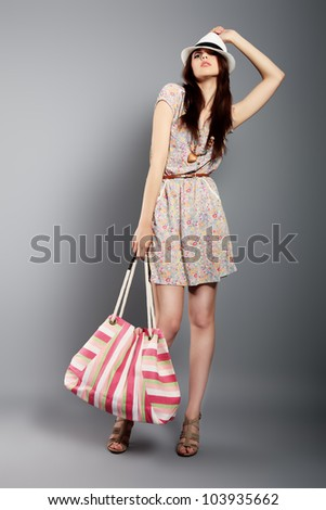 Shot of a beautiful girl in summer style posing at studio. - stock photo