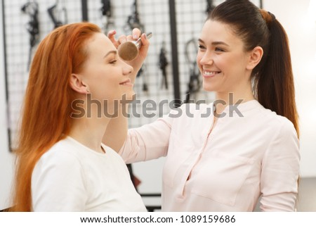 Shot of a beautiful happy female professional makeup artist working at the beauty salon applying makeup on her client. Cheerful young woman talking to a beautician while having her visage done