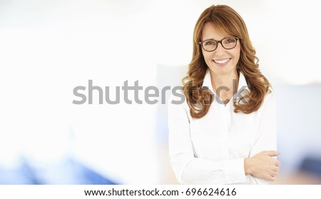 Shot of a beautiful middle aged professional woman standing at the office while looking at camera and smiling.  #696624616