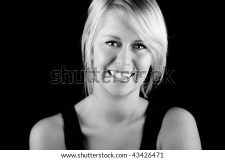 Shot of a Beautiful Smiling Blonde Girl against Dark Background - stock photo