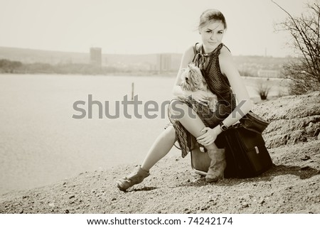 Shot of a beautiful woman sitting on suitcase on the banks of the lake with the dog (Yorkshire terrier). In Black & White