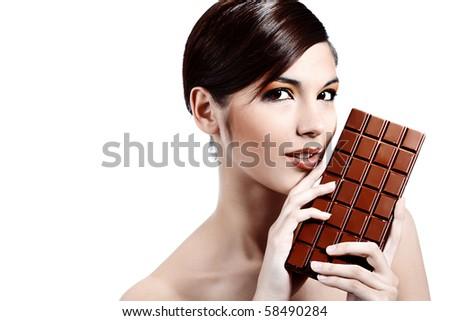 Shot of a beautiful young woman holding big chocolate bar.