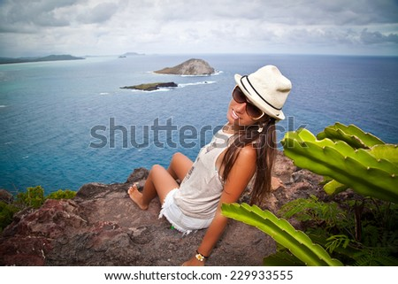 Shot of a beautiful young woman smiling while taking a break from hiking through the mountains. Adventurous and carefree. View of the Windward side of O'ahu. #229933555