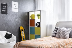 Shot of a bedroom interior with a single bed and colorful shelf